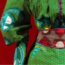 detail of a green dress with red belt against red background