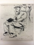 man with hat and glasses seated outside reading