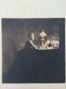 woman seated at desk with table light