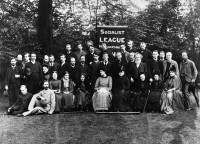 portrait of a group of men and women with Socialist League banner behind them in a garden