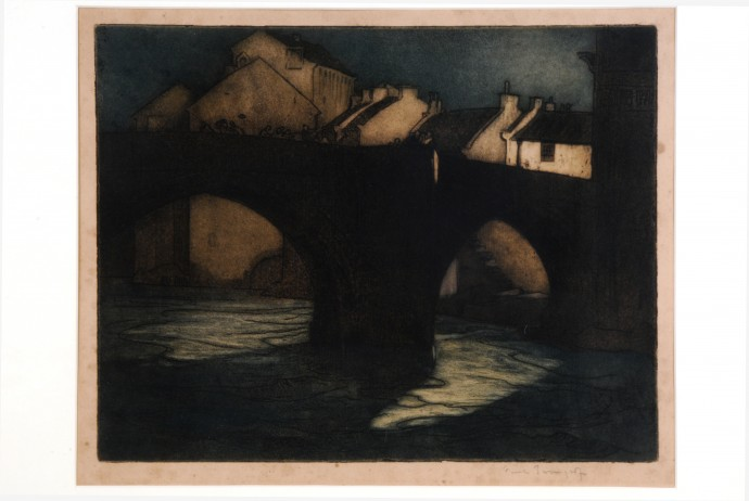 Dark bridge over river with cottages beyond
