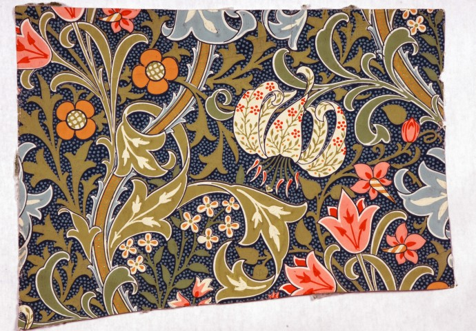 fragment of wallpaper with green pink orange and blue flowers on dark blue ground